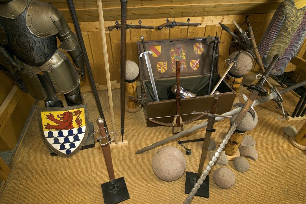 Burg Rötteln, Burgmuseum, Funde (Kanonenkugeln, Stein) aus dem Bereich der Burg Rötteln neben Rüstung und Wappenschild