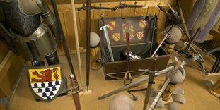 Funde (Kanonenkugeln, Stein) aus dem Bereich der Burg Rötteln neben Rüstung und Wappenschild im Burgmuseum