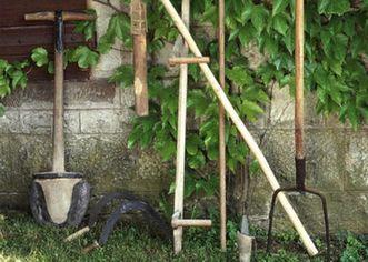 Bäuerliche Arbeitsgeräte, wie Sense oder Spaten, vor mit wildem Wein bewachsenem Gebäude
